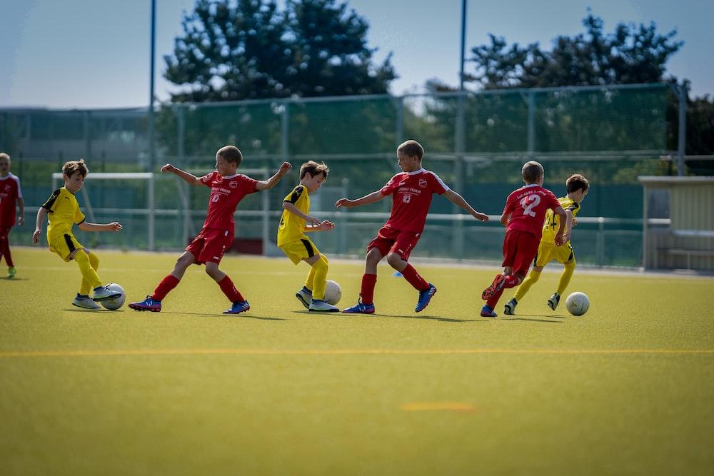 group of men playing soccer during daytime