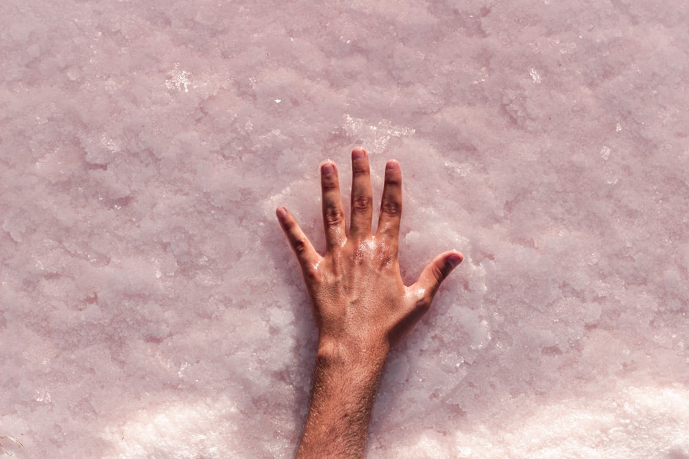 persons left hand on gray concrete floor