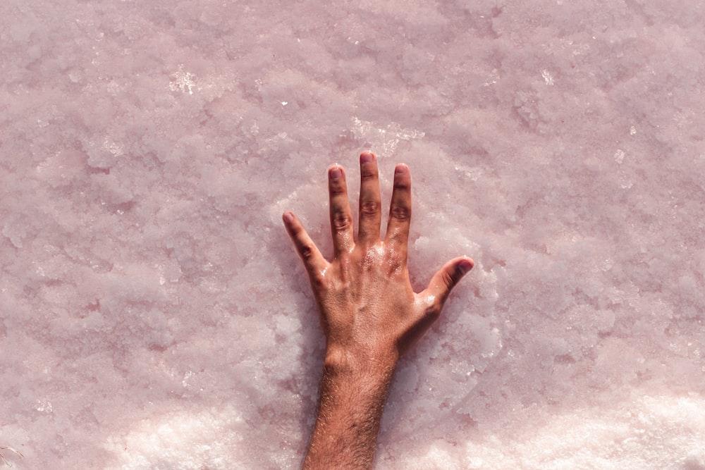 persons left hand on gray concrete floor