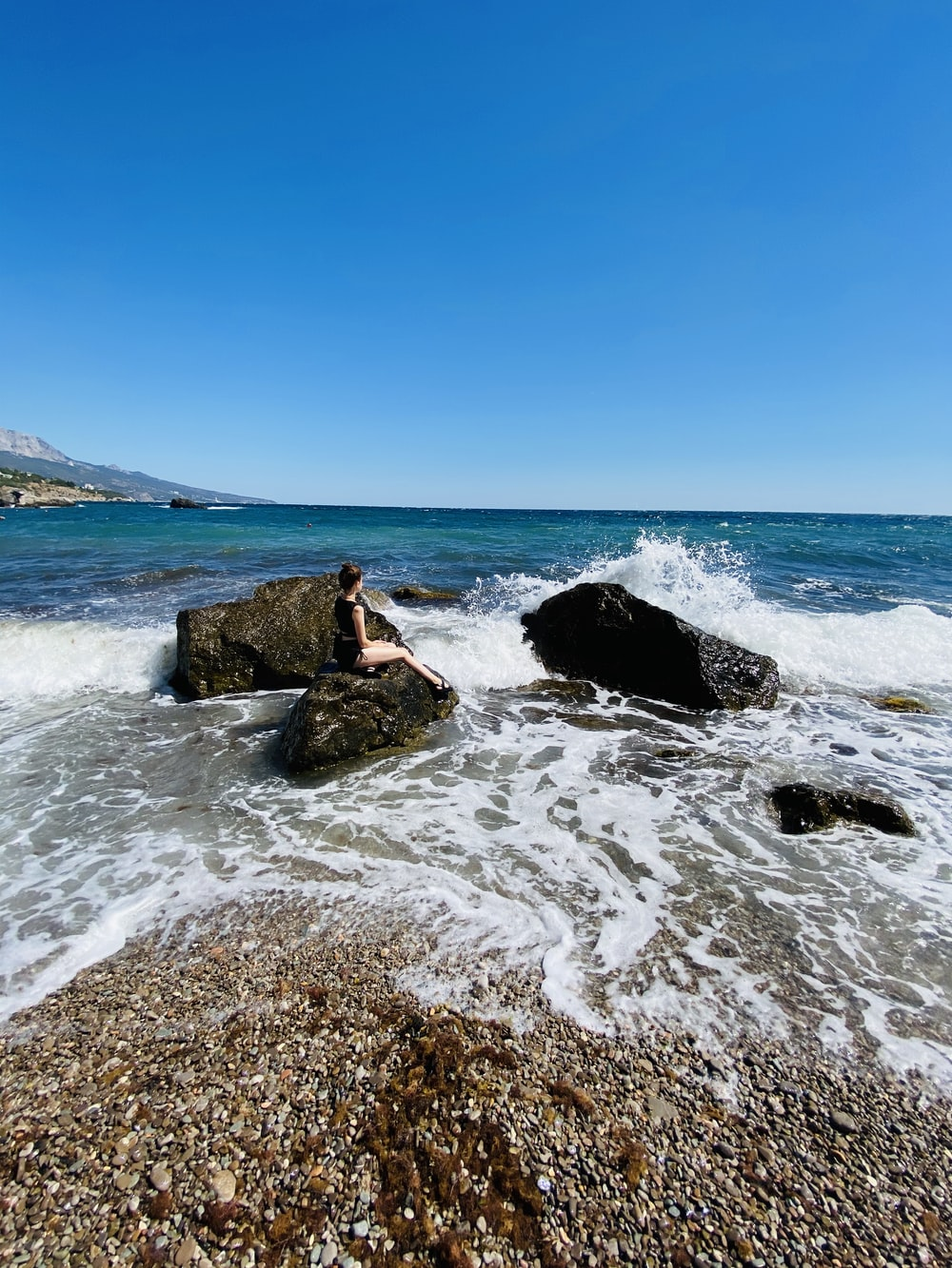 woman in black dress sitting on rock formation on sea during daytime