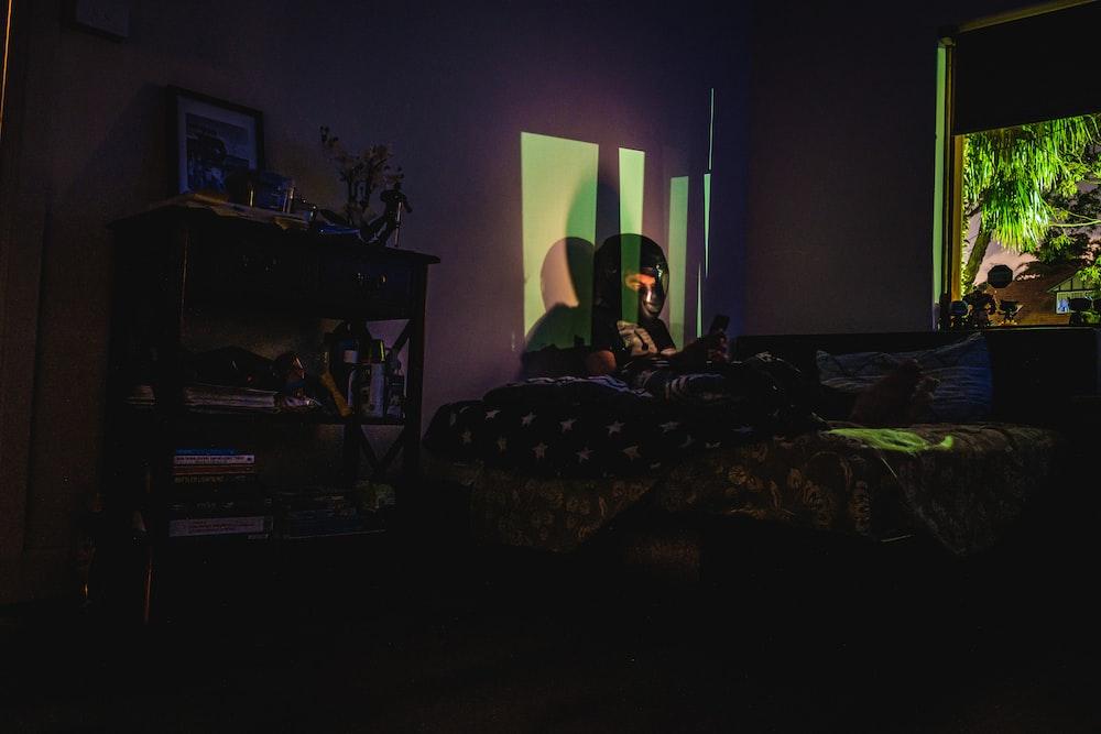 black flat screen tv turned on near bed