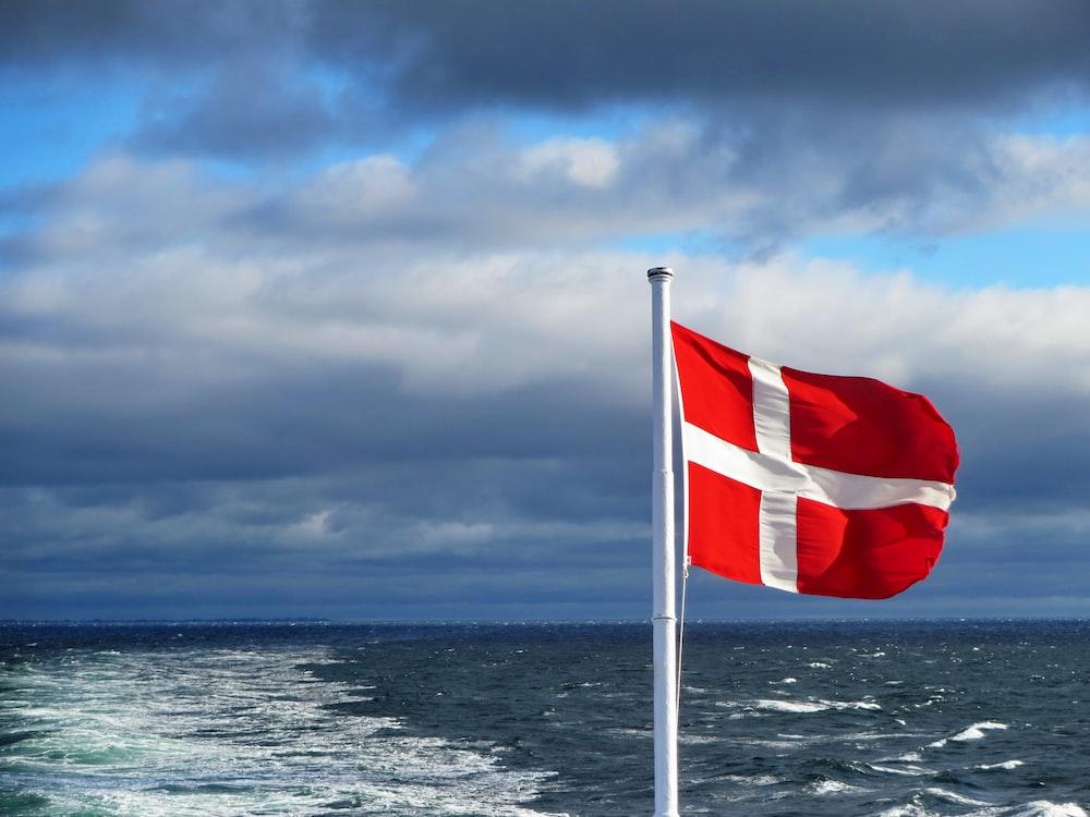 us a flag on flag pole near sea under cloudy sky during daytime