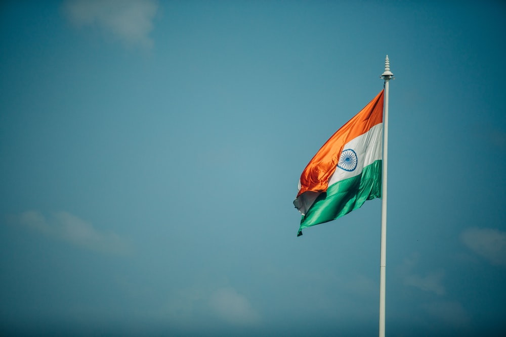 orange white and green flag under blue sky during daytime