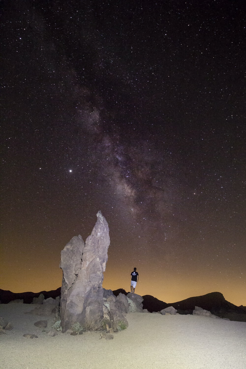 silhouette of people standing on mountain under starry night