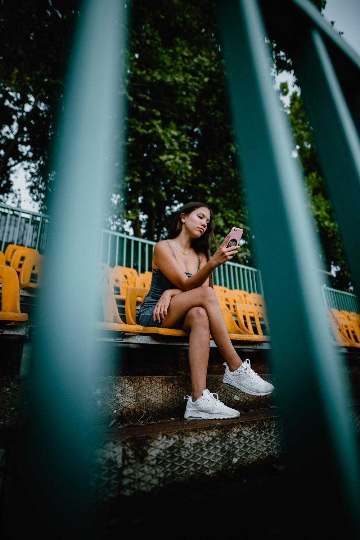 2 women sitting on black metal fence during daytime