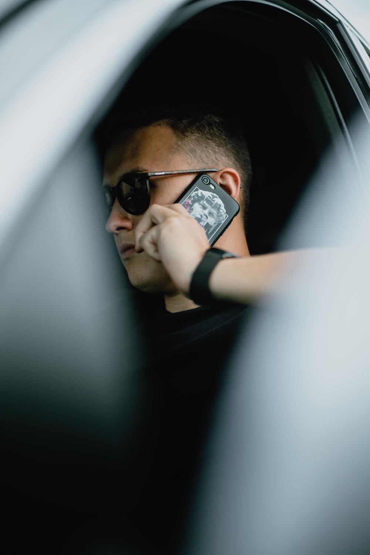 man in black shirt wearing black sunglasses holding black smartphone