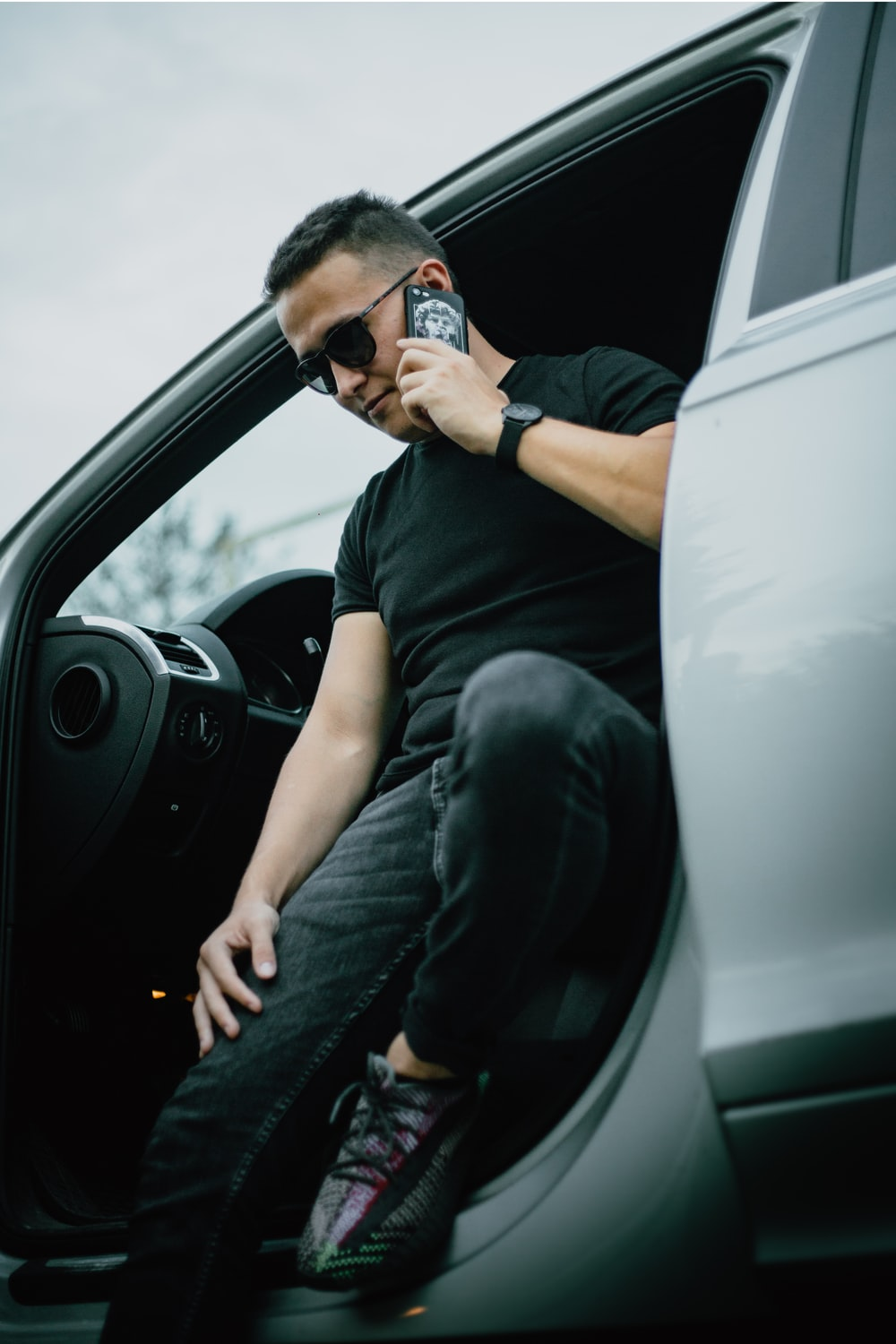 man in black t-shirt and blue denim jeans sitting on drivers seat