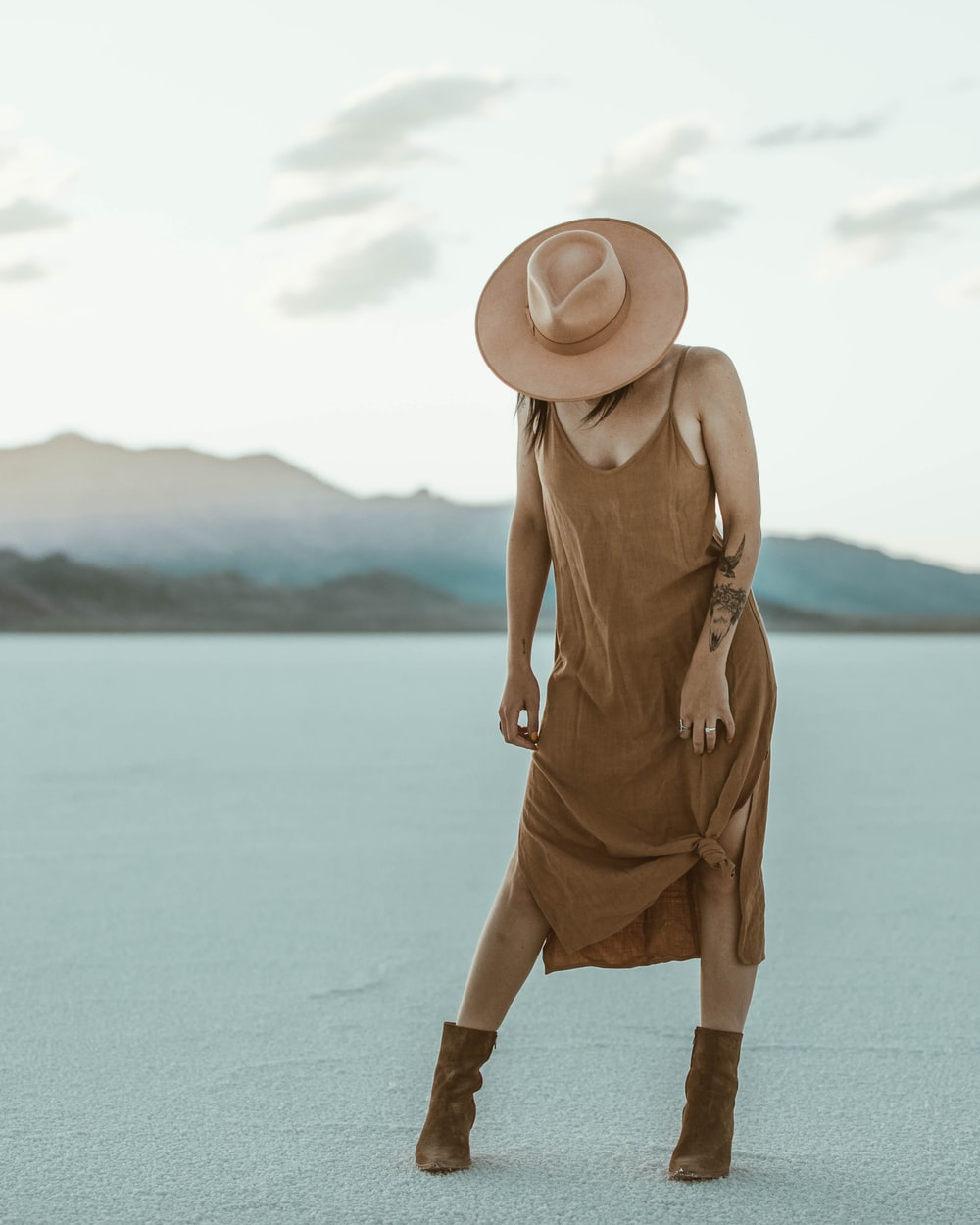 woman in brown dress wearing brown sun hat standing on white sand during daytime