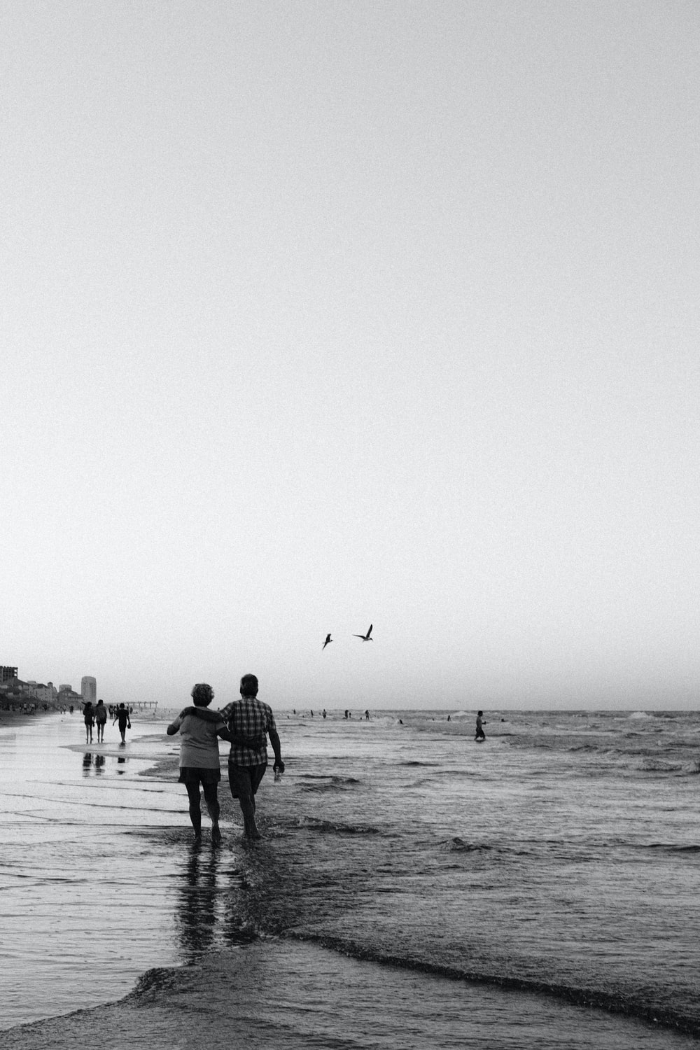 grayscale photo of people walking on beach