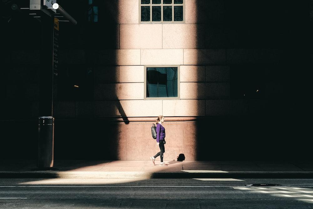 girl in pink jacket and pants walking on sidewalk during daytime