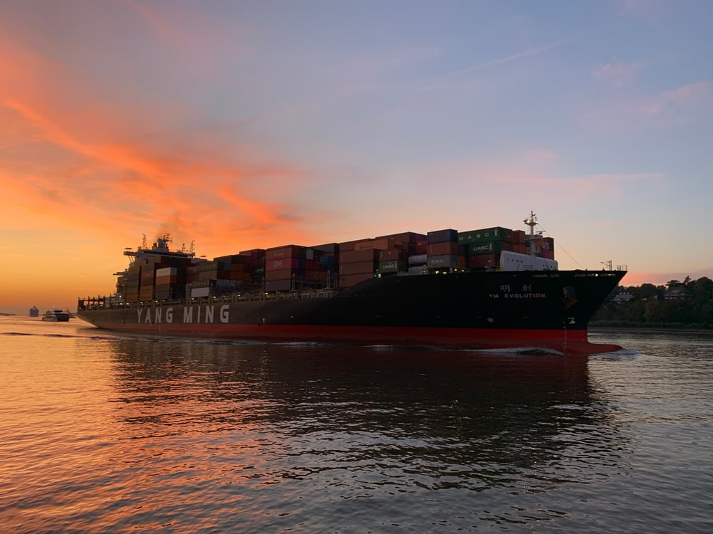 red cargo ship on sea during sunset