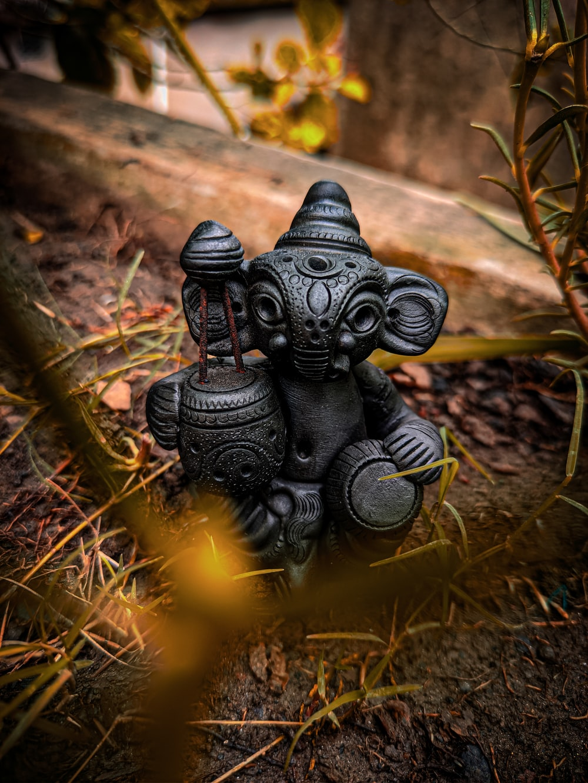 black frog figurine on brown dried leaves