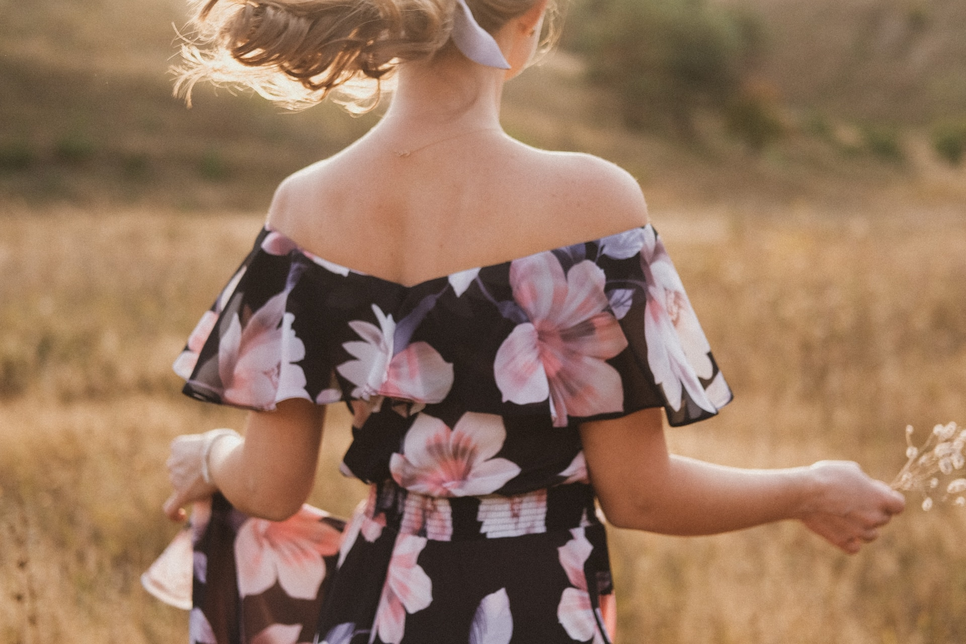 girl in black and pink floral dress standing on brown grass field during daytime