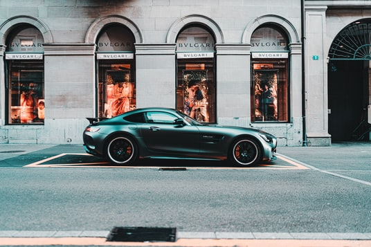 black coupe parked in front of building