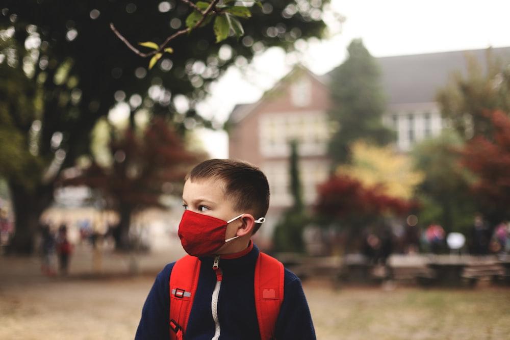 boy in red and blue jacket wearing black framed eyeglasses