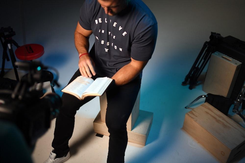 man in black crew neck t-shirt holding white paper