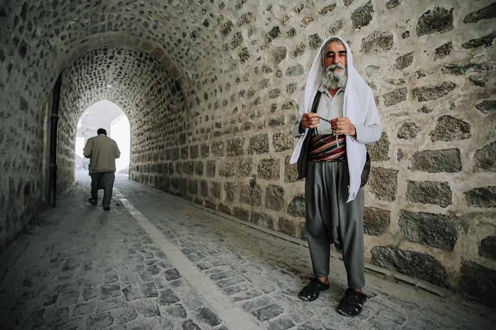 man in white thobe standing on gray concrete floor