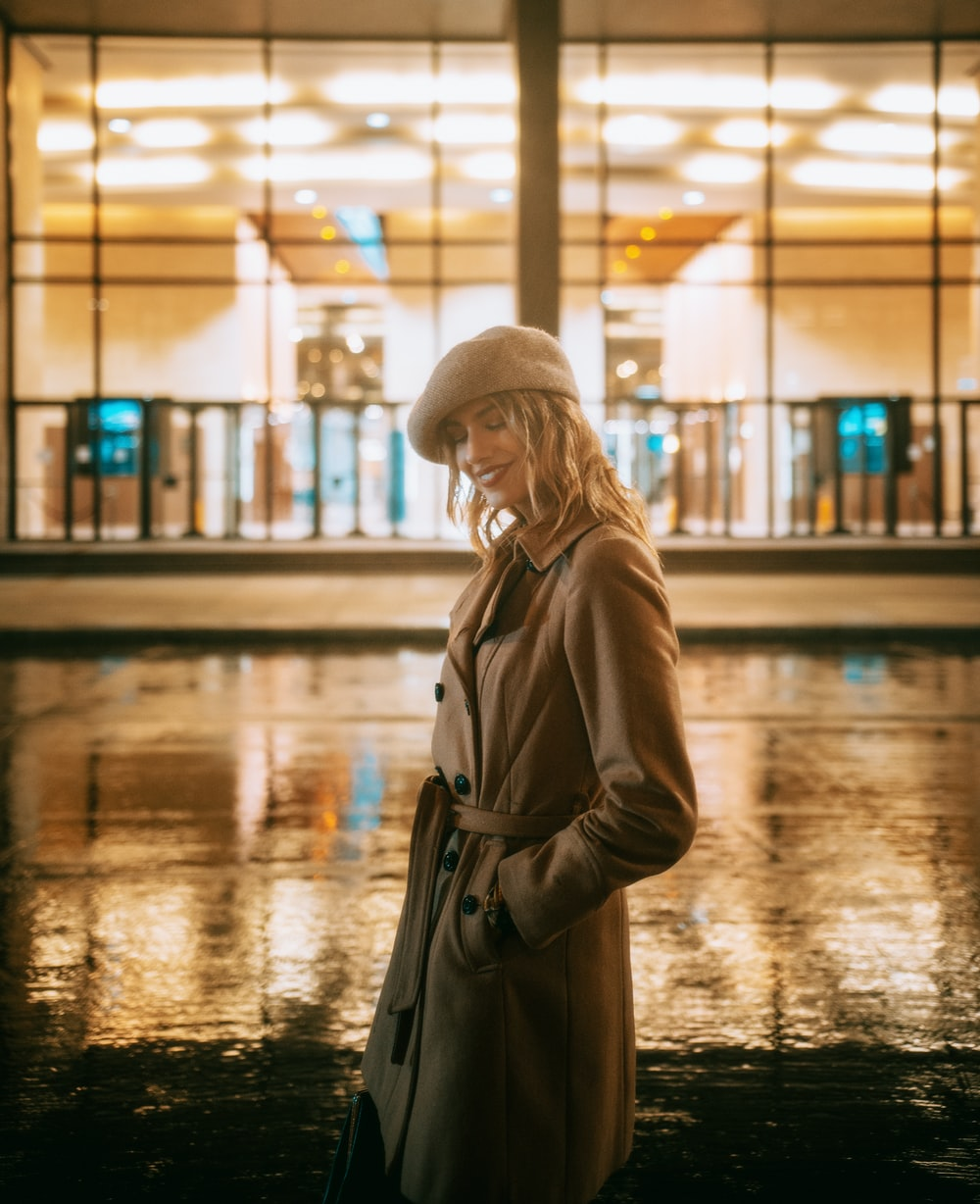 woman in brown coat and white knit cap standing on wet ground during night time