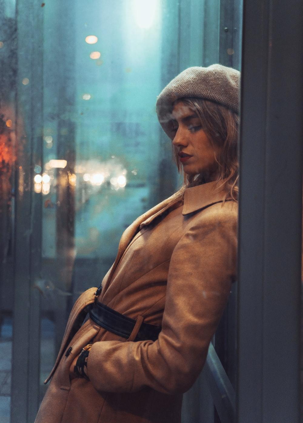 woman in brown coat standing beside glass window