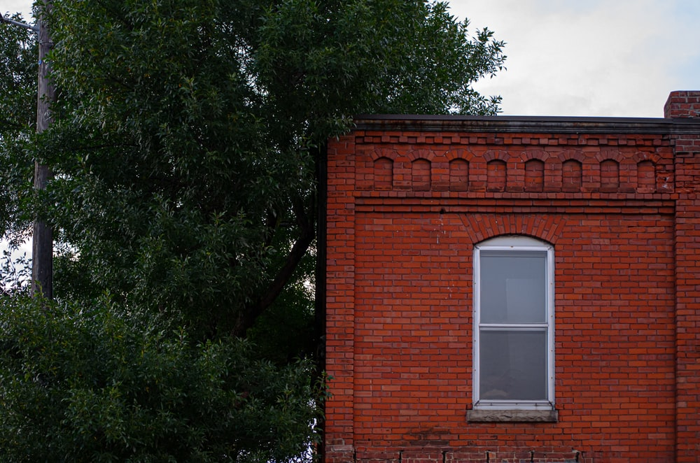 brown brick building with white window frame