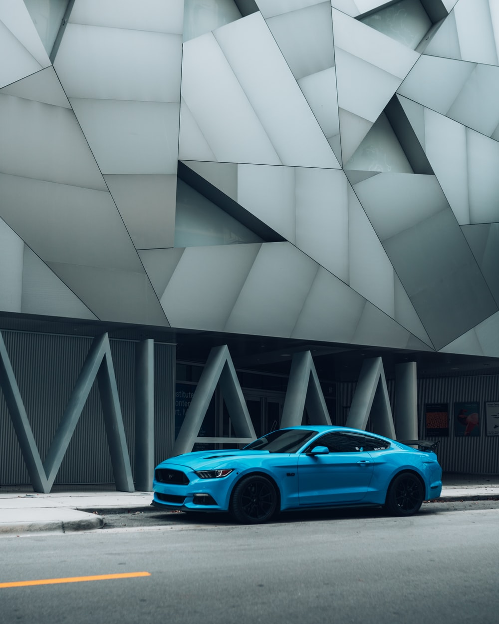 blue coupe parked beside gray building