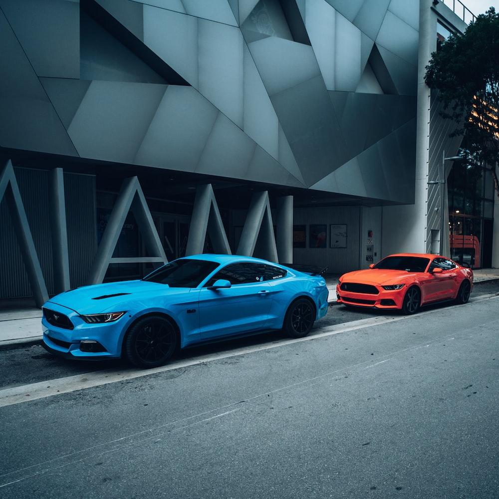 blue coupe parked beside orange car