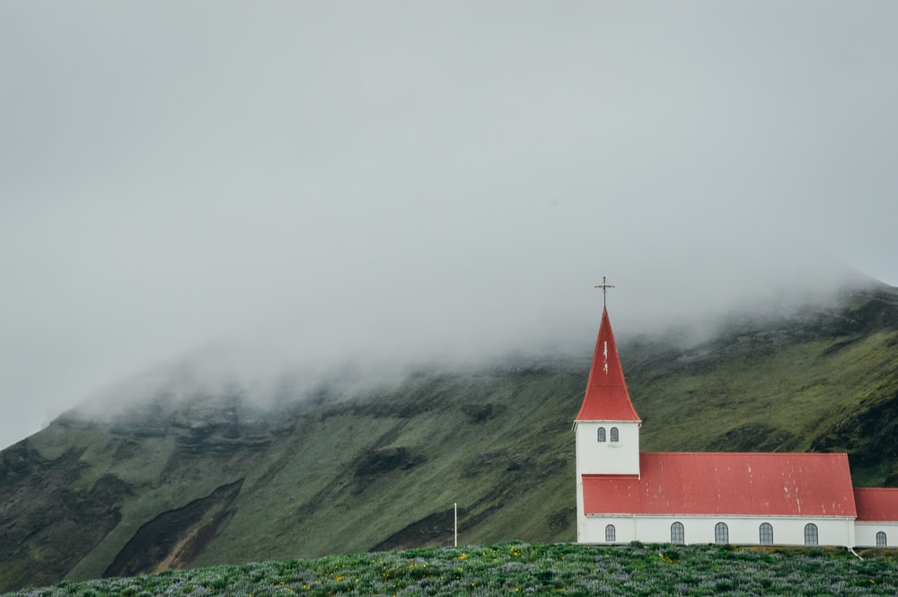 red and white concrete church on green grass field