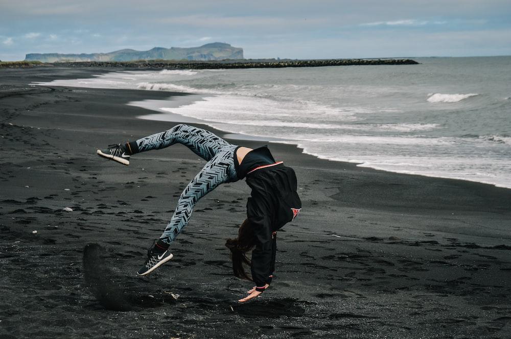 man in black jacket and black pants walking on beach shore during daytime