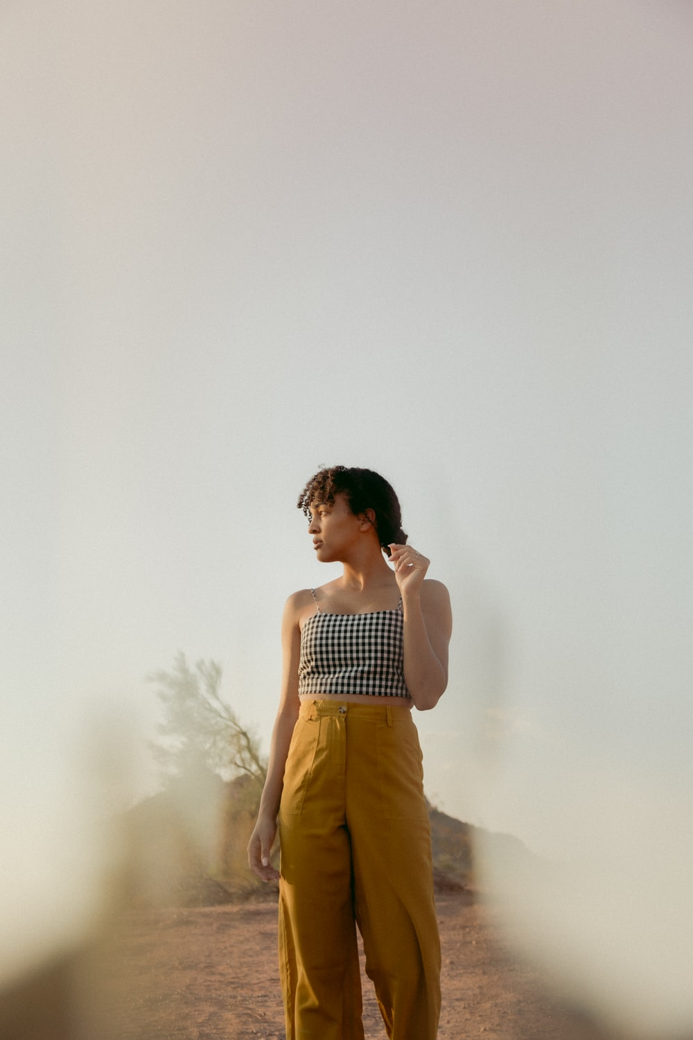 woman in white and black stripe tank top and brown pants standing near white wall
