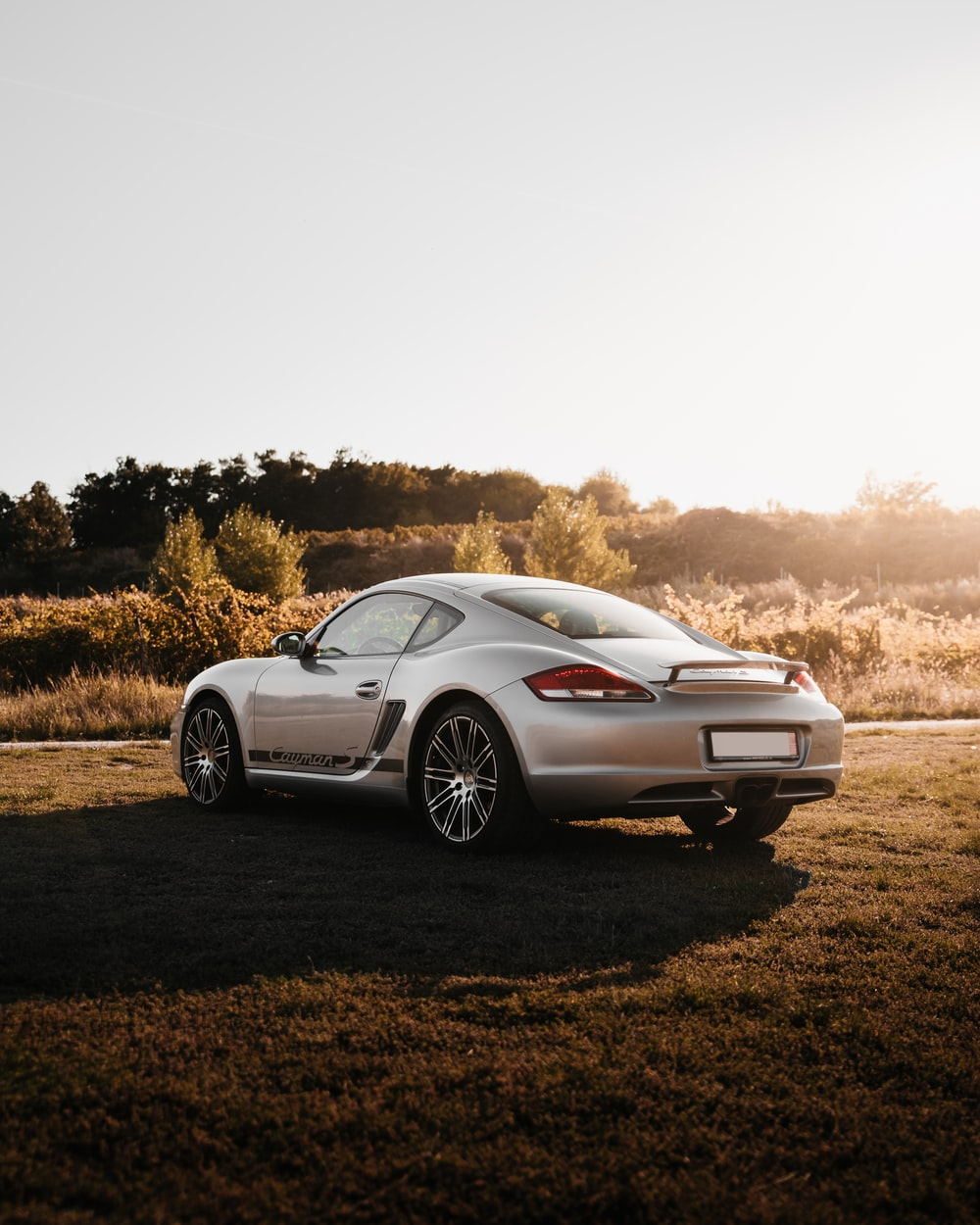white porsche 911 on brown field during daytime