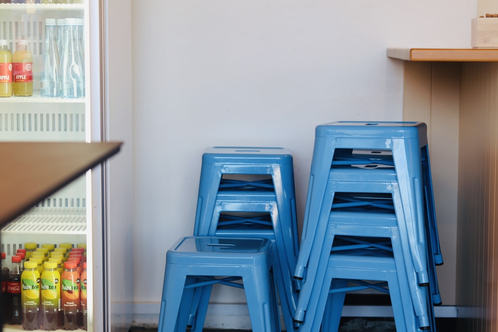 blue plastic chairs beside brown wooden table