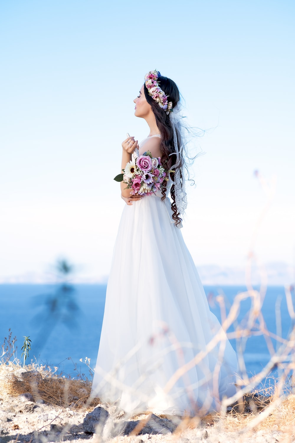 woman in white wedding dress standing on brown grass field during daytime