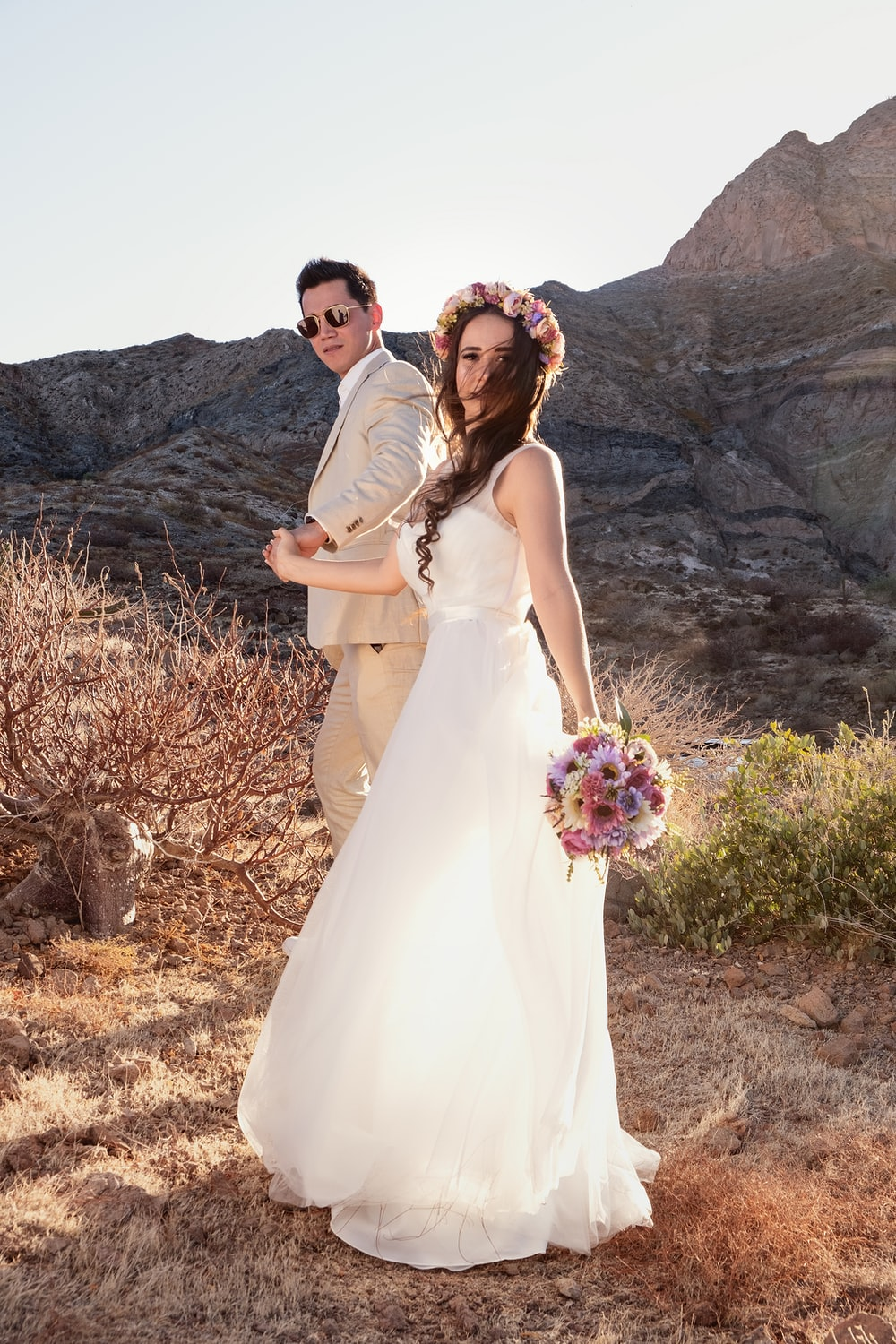 man and woman in wedding dress standing on brown grass field during daytime