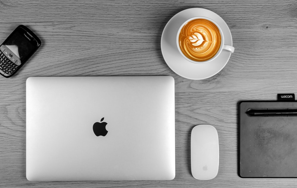 white ceramic cup with saucer beside silver macbook
