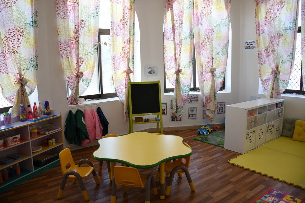 a preschool classroom with pink curtains