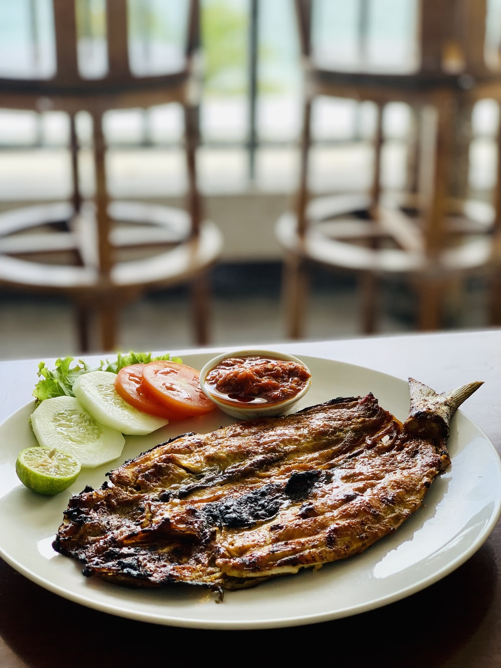grilled meat with sliced cucumber and sliced cucumber on white ceramic plate