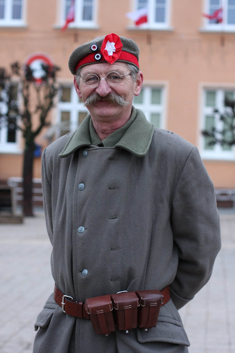 man in green coat wearing red cap standing on street during daytime