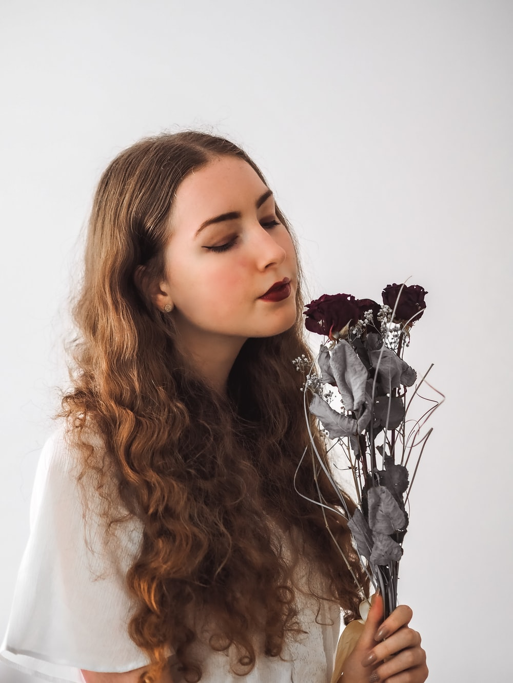 woman in white shirt with silver flower headband