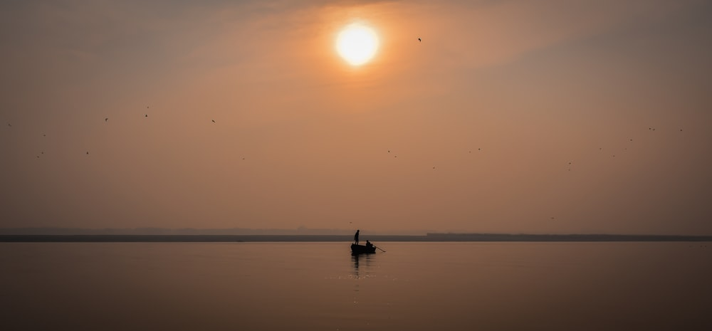 silhouette of person riding boat on sea during sunset