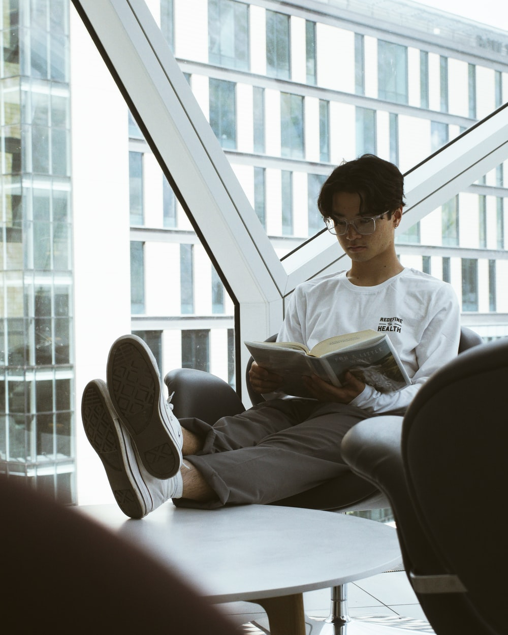 man in white crew neck t-shirt sitting on black leather chair