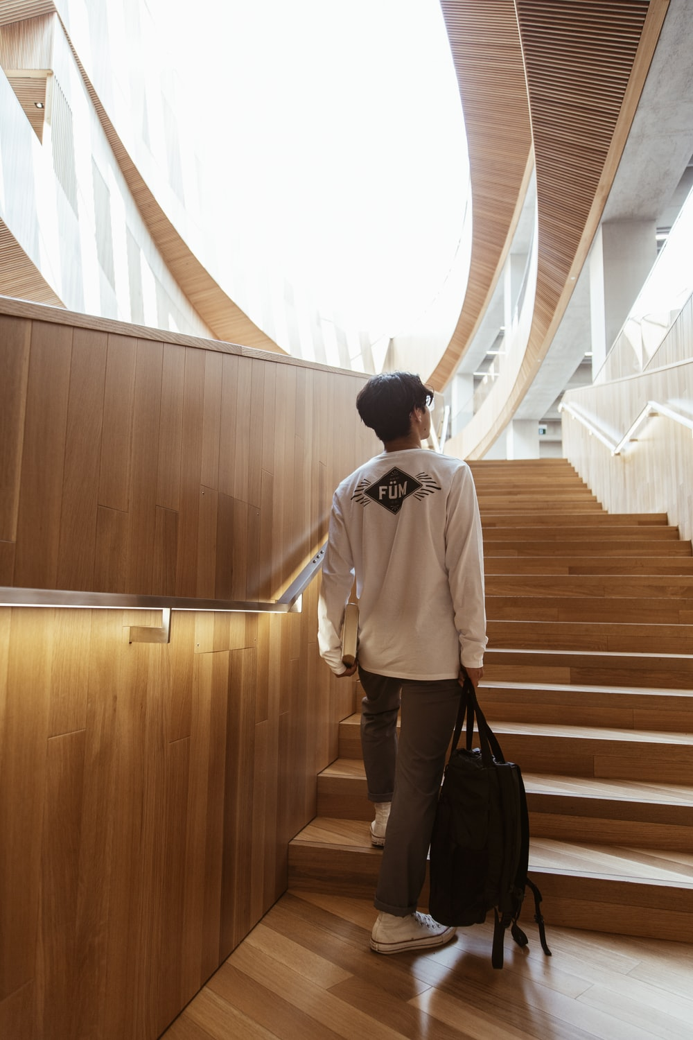 man in white dress shirt and black pants standing on brown wooden staircase