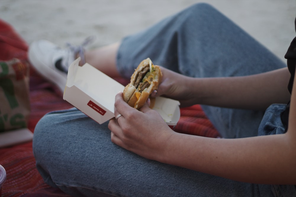 person holding burger with fries