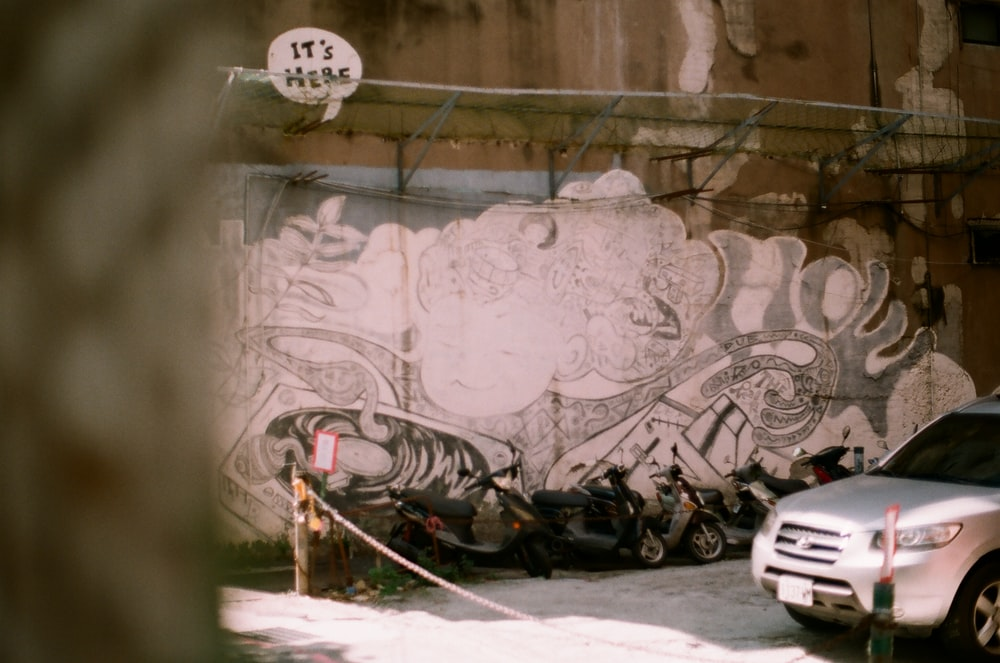 black motorcycle parked beside wall with graffiti