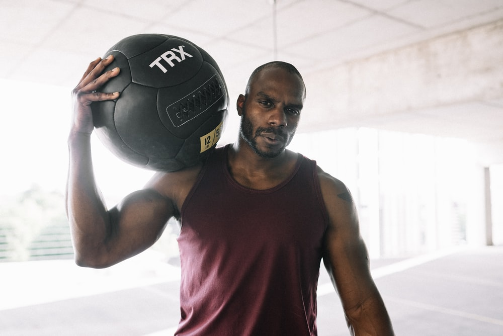 man in red tank top holding black and white soccer ball