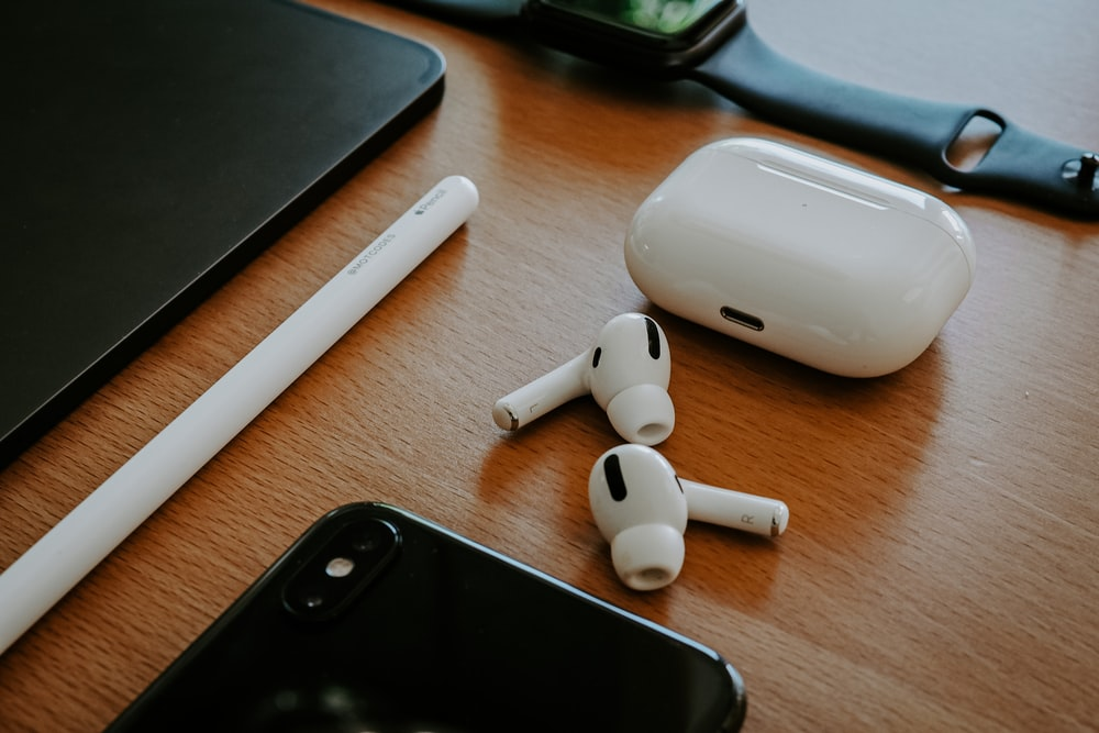 white apple earpods beside black iphone 5