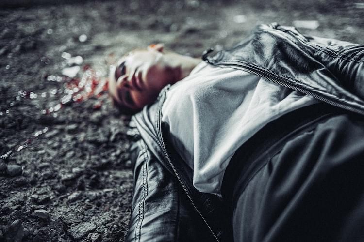 ¿Se muere en manos de o a manos de?