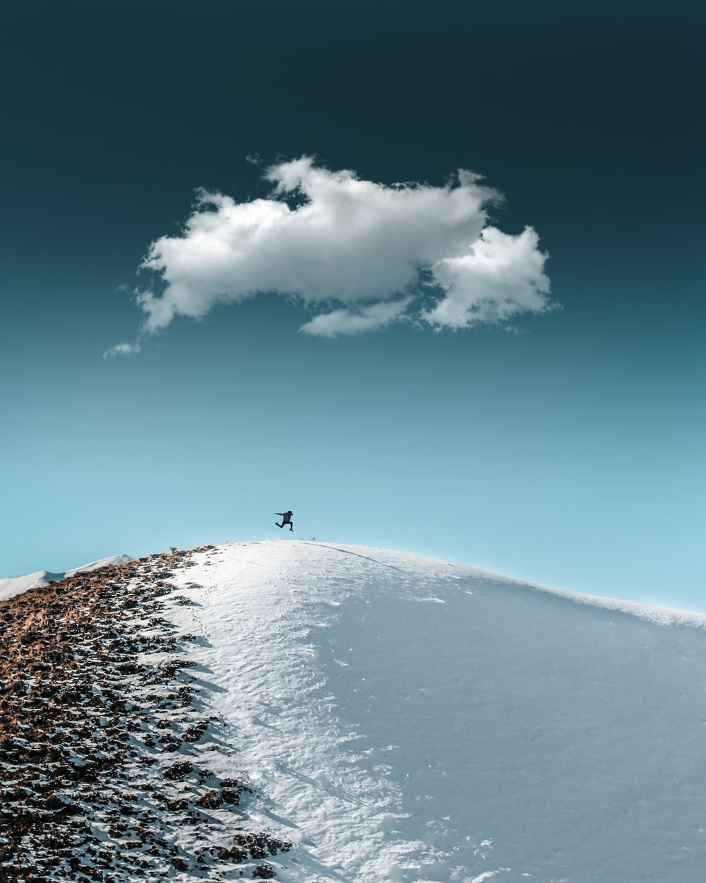 person standing on snow covered ground under blue sky during daytime