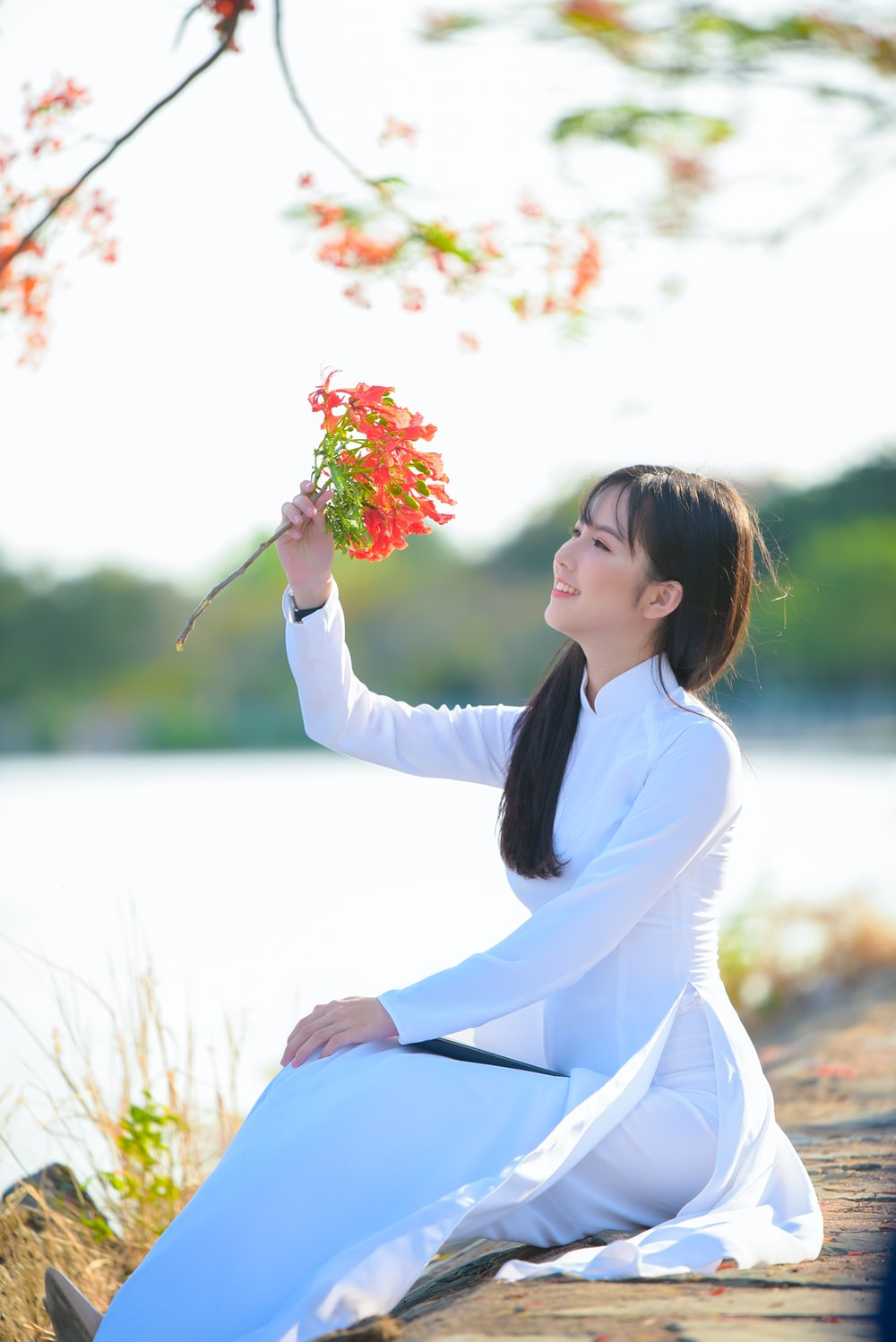 woman in white long sleeve dress holding pink flowers