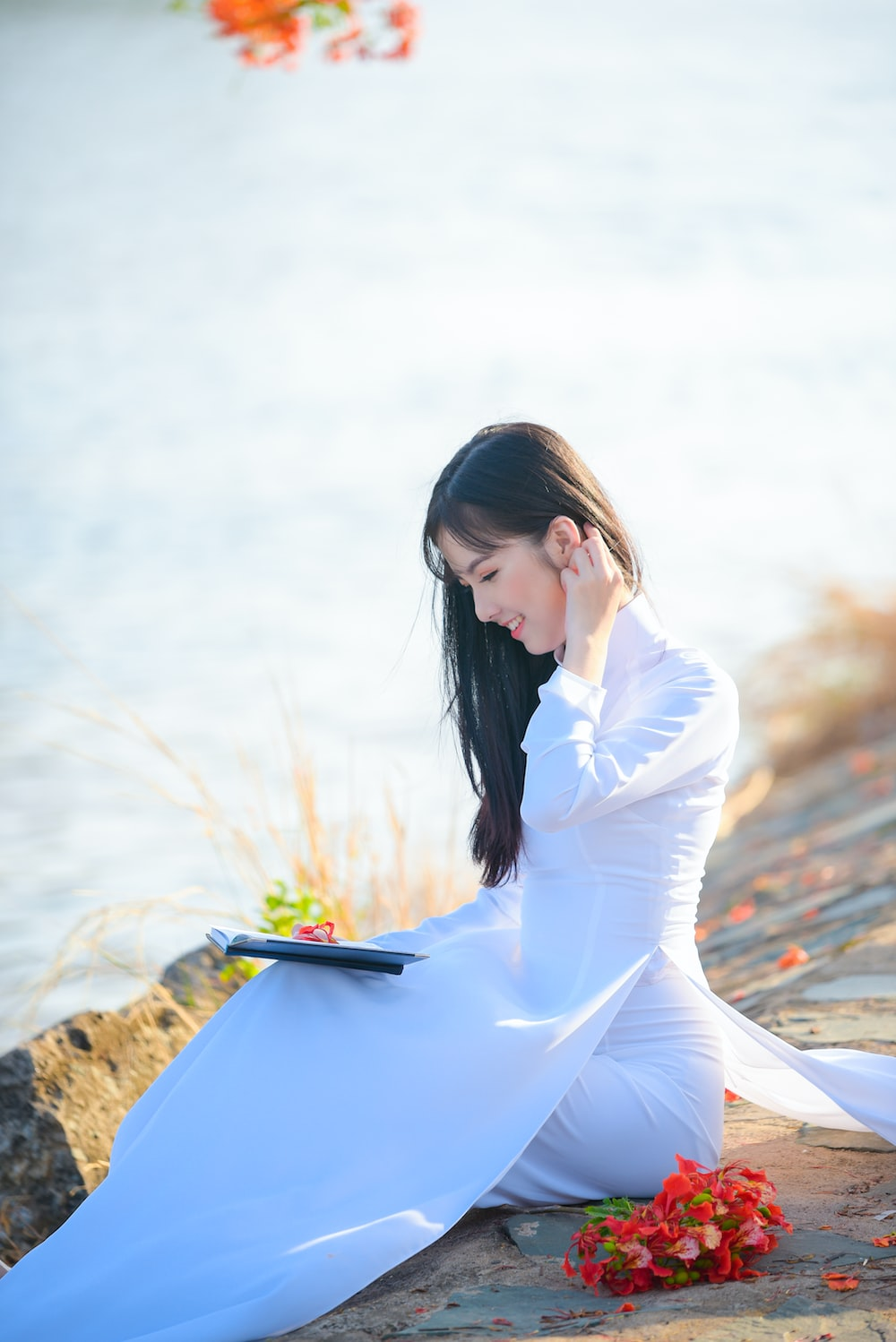 woman in white long sleeve dress sitting on brown rock during daytime