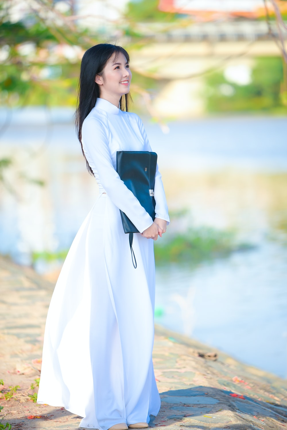 woman in white long sleeve dress holding black book
